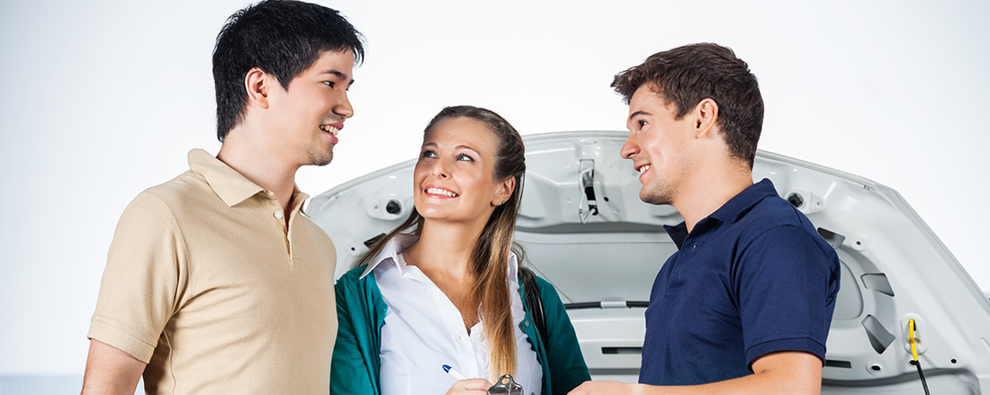 Happy couple discussing with mechanic while signing on document at garage